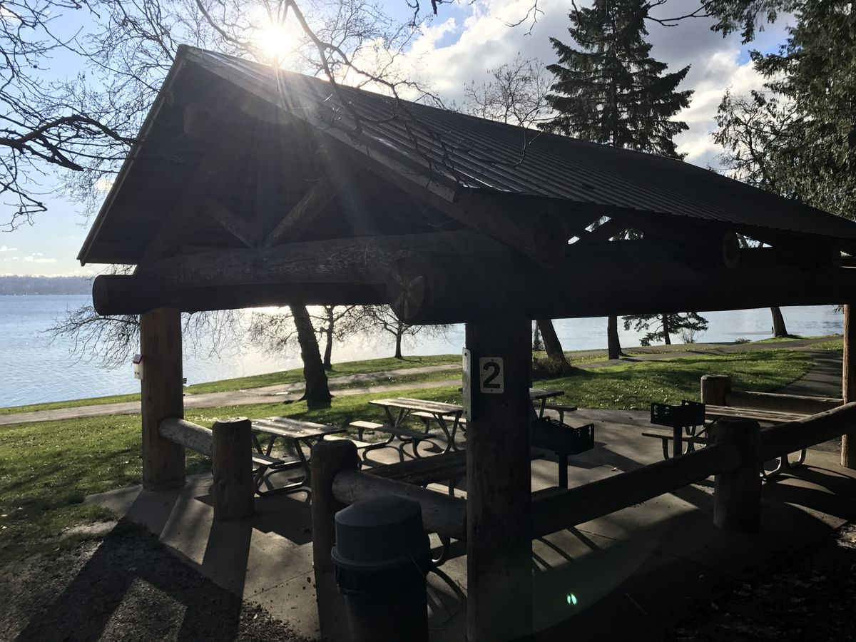 A large picnic shelter with tables and grills inside and a lake in the background.