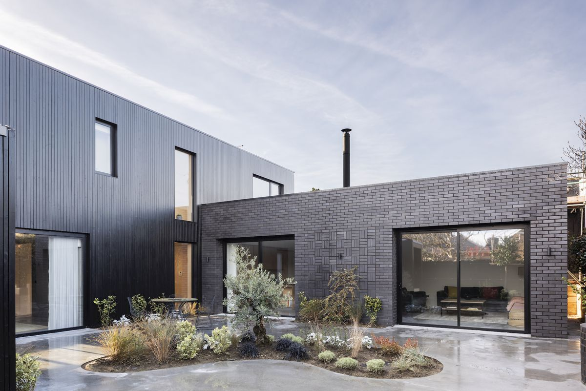 All-black modern house centered around a plant garden.