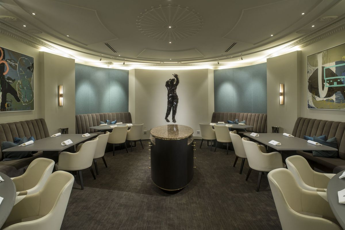 One of Alinea's dining areas is modern with light off-whites and a central statue.