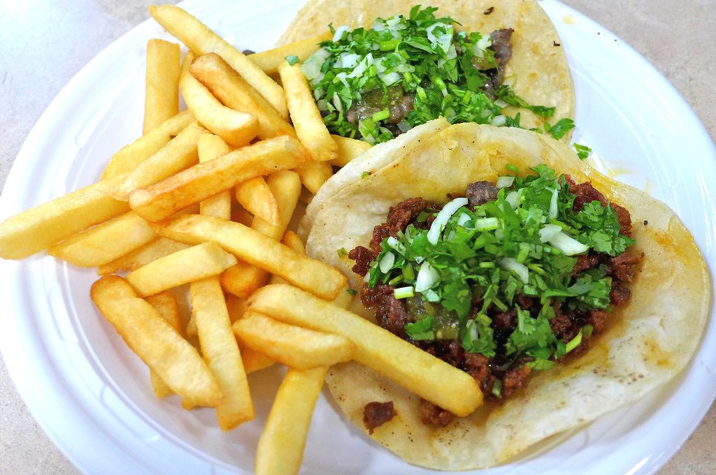 Two meat tacos with french fries crowding them on the plate.