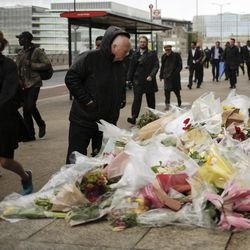 A man looks at flowers on a memorial for victims at the London Bridge in London, Tuesday, June 6, 2017. British police on Tuesday named the third London Bridge attacker as an Italian national of Moroccan descent, and Italian officials said they had passed on their concerns about him to British intelligence officials last year.
