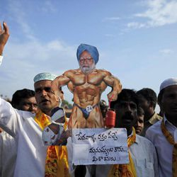 """Activists of Telugu Desam Party (TDP) carry a caricature of Indian Prime Minister Manmohan Singh with the words """"the blood suckers are not human beings but devils"""" during a protest at a bus station in Hyderabad, India, Thursday, Sept. 20, 2012. Angry opposition workers have disrupted train services as part of a daylong strike in India to protest rising diesel prices and the government's decision to open the country's huge retail market to foreign companies."""