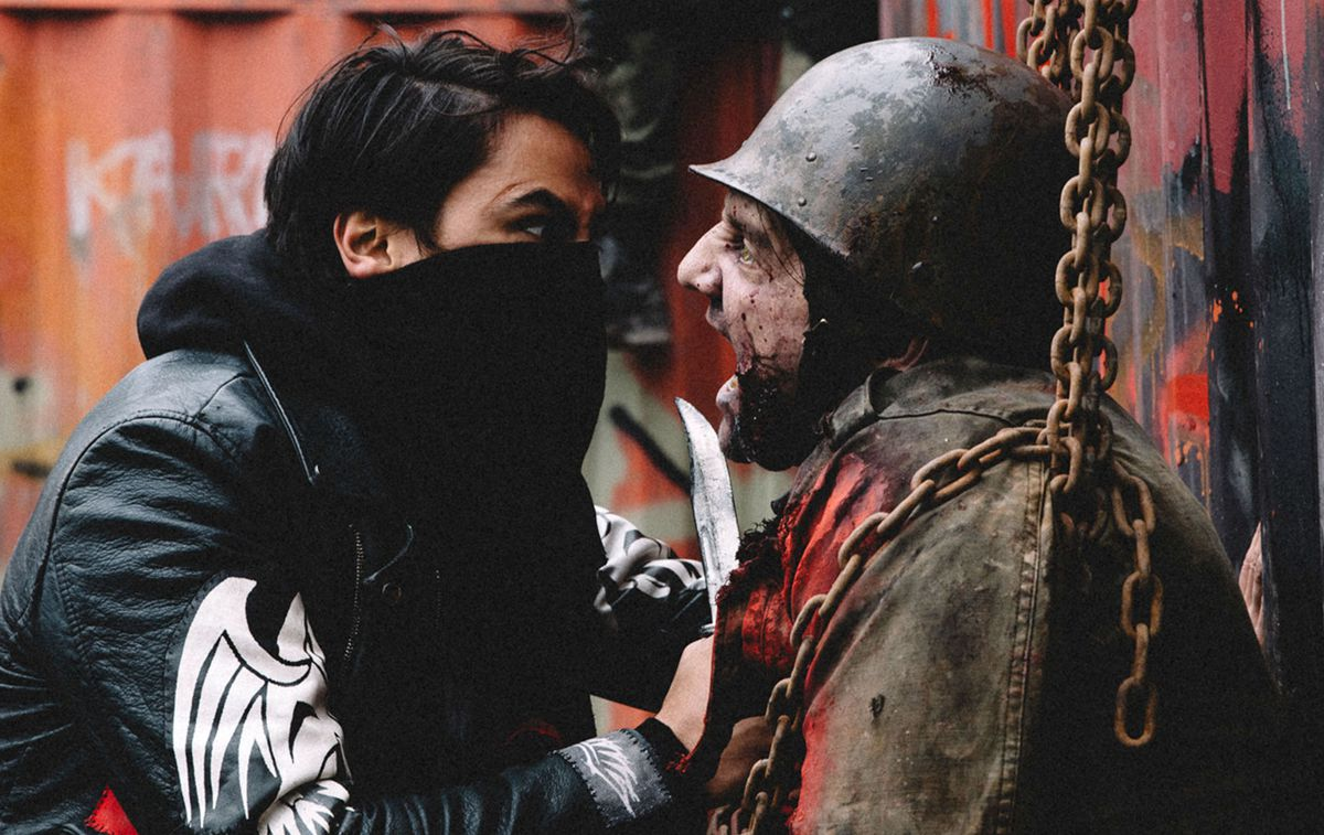 A masked man holds a knife up to a zombie soldier in Blood Quantum