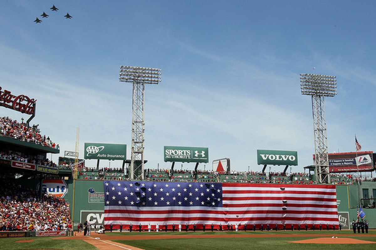 BOSTON - JULY 04:  Jets fly over as a giant flag covers the Green Monster before the game between the Baltimore Orioles and  the Boston Red Sox on July 4 2010 at Fenway Park in Boston Massachusetts.  (Photo by Elsa/Getty Images)