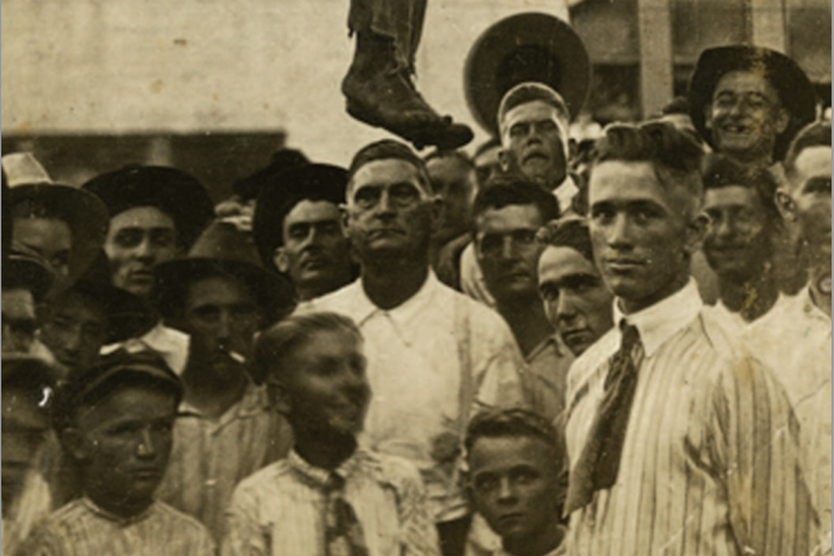 White men and boys pose beneath the body of Lige Daniels shortly after he was lynched on August 3, 1920, in Center, Texas.