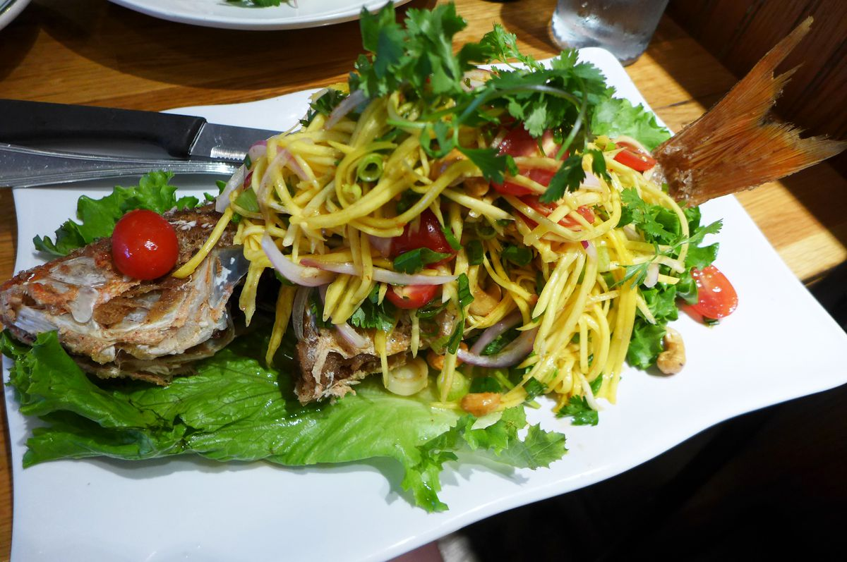 A fried whole fish with a pile of yellow papaya salad comes on top of lettuce on a white plate.