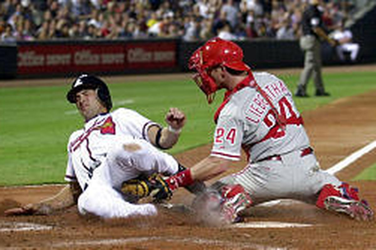 Braves' Mark DeRosa is tagged out at home by Phillies catcher Mike Lieberthal in third inning Tuesday.