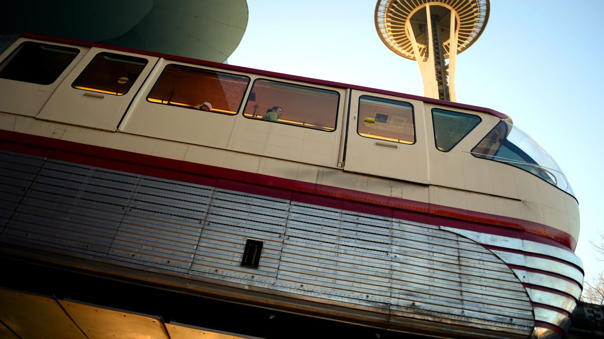 A monorail train exits a tunnel under a blue sky and a tall building with a saucer on top (the Space Needle).
