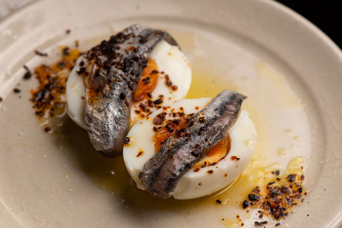 Two soft boiled eggs with anchovy and olive oil on top.