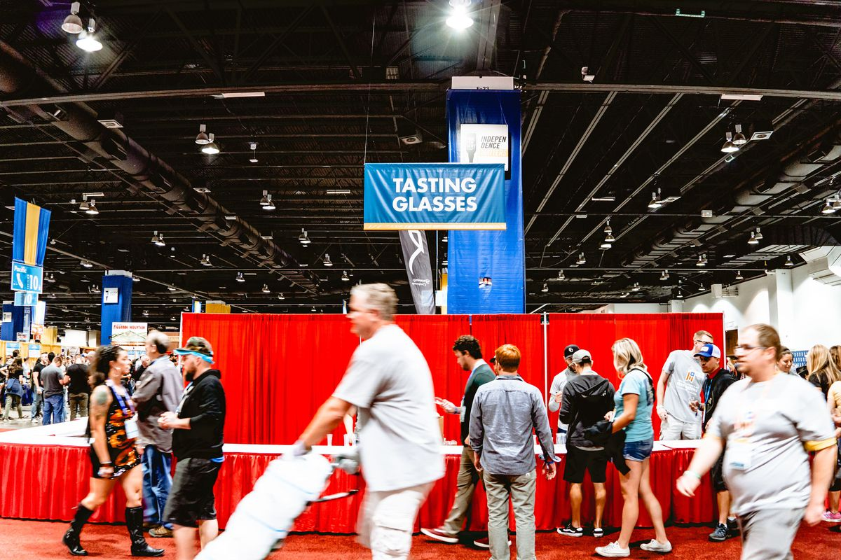 A photo of several Great American Beer Festival attendees walking in front of the table where tasting glasses were given out at the Friday night session of the festival