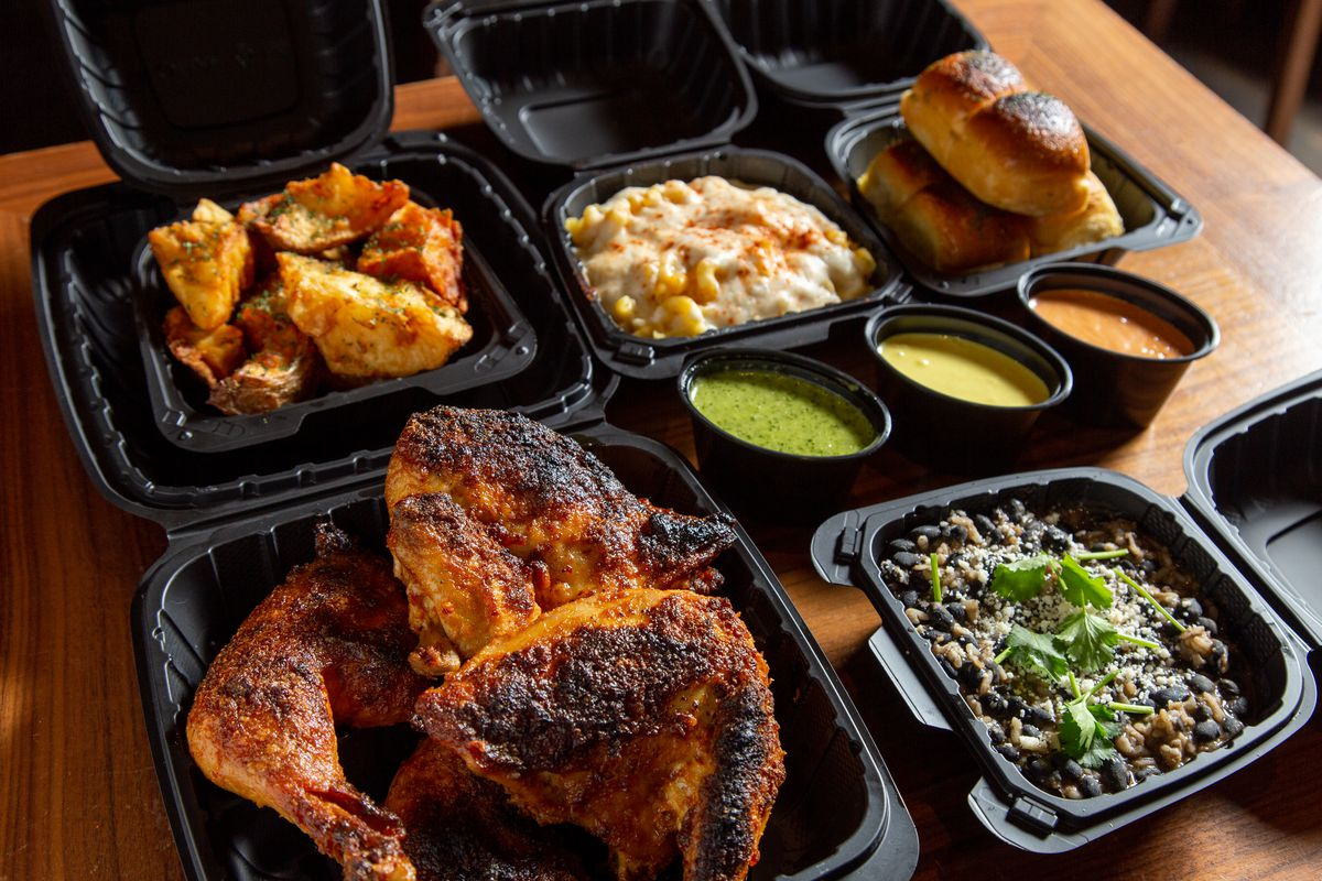Rotisserie chicken and sides in black to-go containers at Chicken Scratch