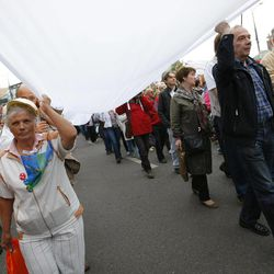 Opposition supporters carry an opposition white flag as they march heading for a protest rally in Moscow, Saturday, Sept. 15, 2012. Thousands of protesters marched across downtown Moscow on Saturday in the first major rally in three months against President Vladimir Putin, while defying the Kremlin's ongoing efforts to crackdown on opposition.
