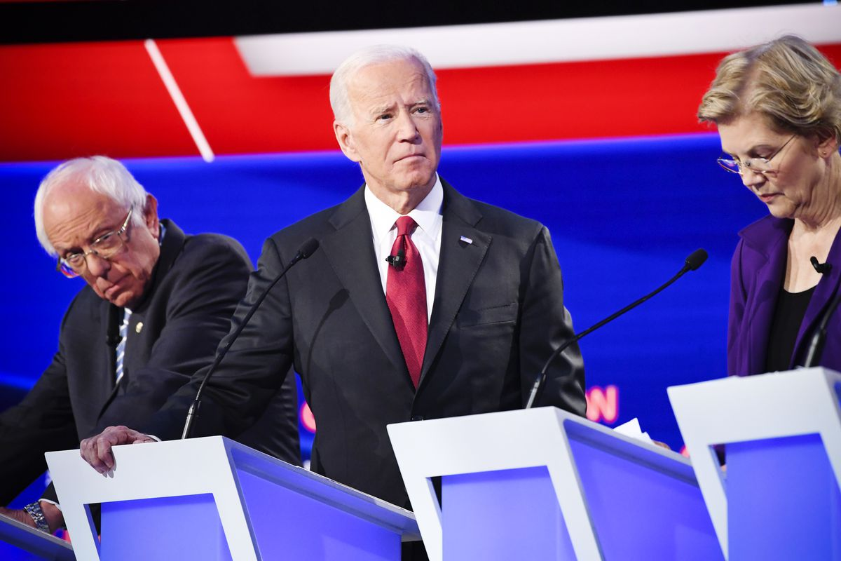 Democratic presidential hopefuls Senator Bernie Sanders, former Vice President Joe Biden, and Senator Elizabeth Warren stand behind podiums at the fourth Democratic primary debate.