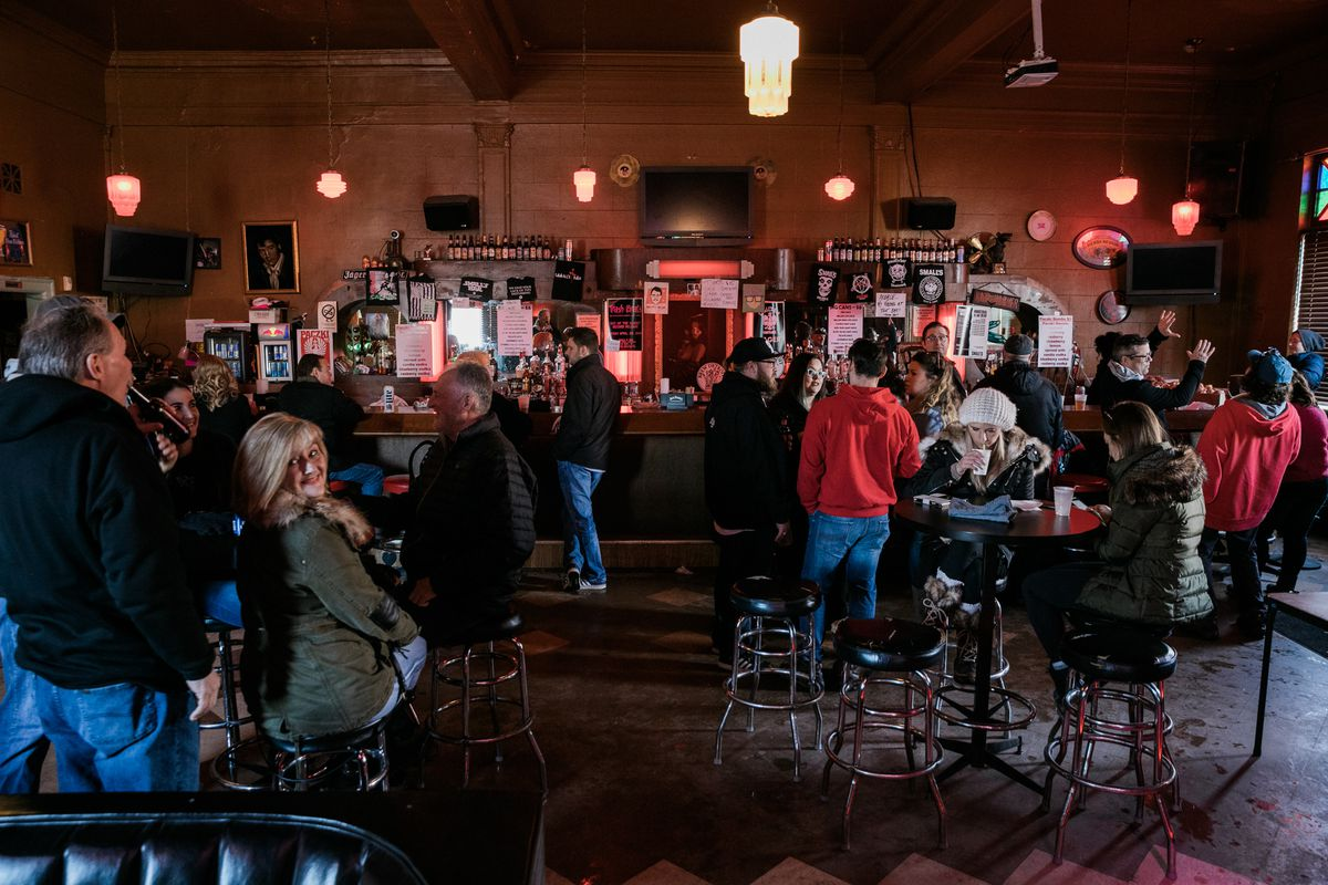 Customers in winter coats sit at tables and stand next to the bar inside Small's.