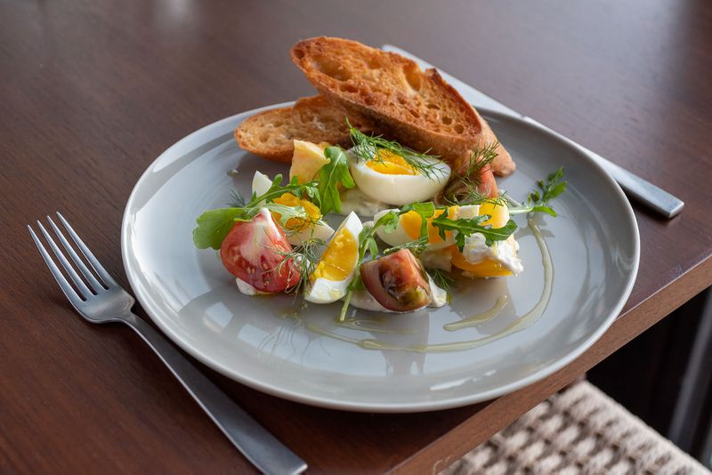 Crispy bread, cooked eggs, tonnato, and tomato on a plate.