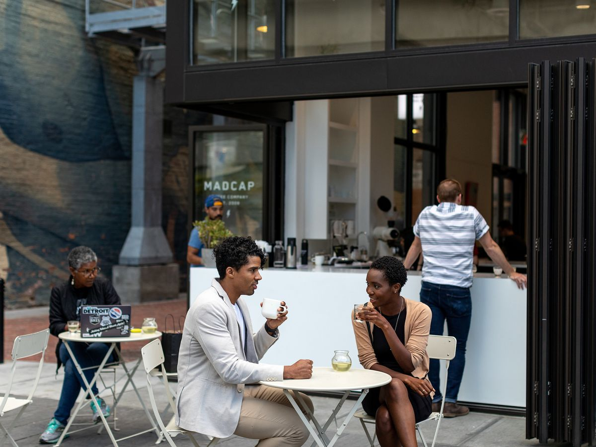 A man and a woman share a table on the patio outside the open bar window at Madcap Coffee on a sunny day.