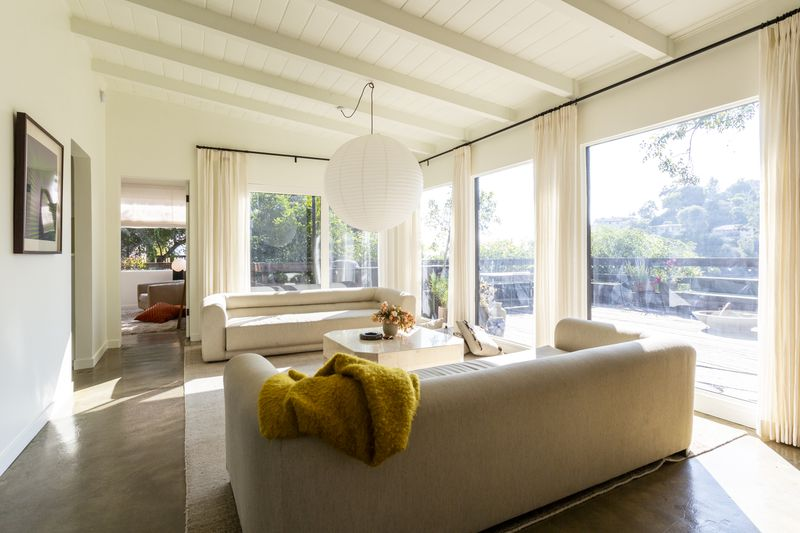Sunny living room with beamed ceilings and walls of glass.