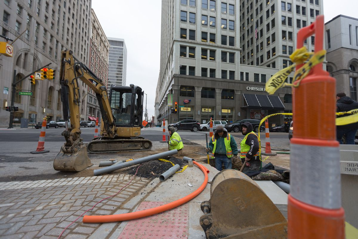 A crew digs up the sidewalk outside Dan Gilbert's Chrysler House building for a high-speed Internet access project.