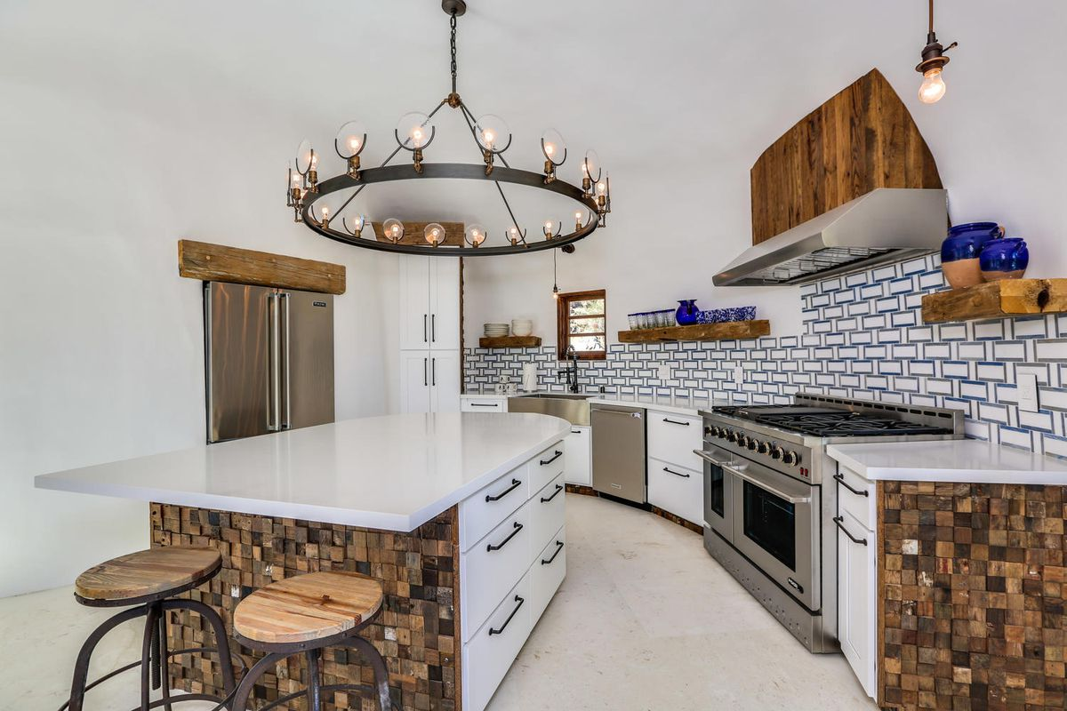A blue and white kitchen has a large white island, chandelier, and wood accents.