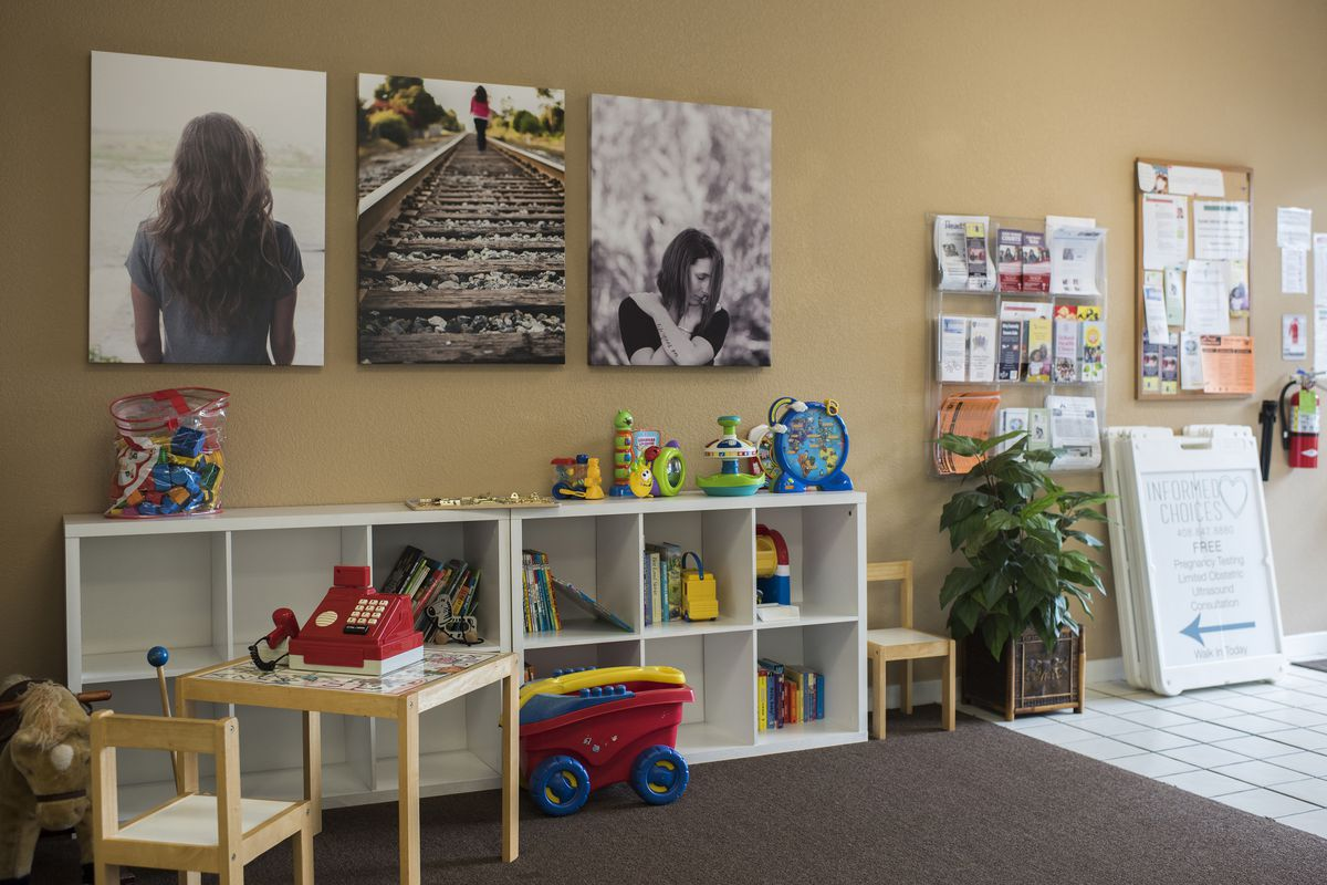 The lobby of a pregnancy resource center, with shelves full of baby toys and artistic photographs of women on the walls.