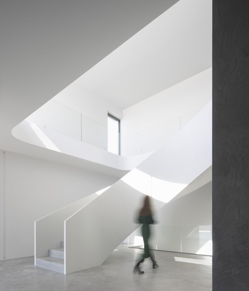 Woman walking next to curved staircase