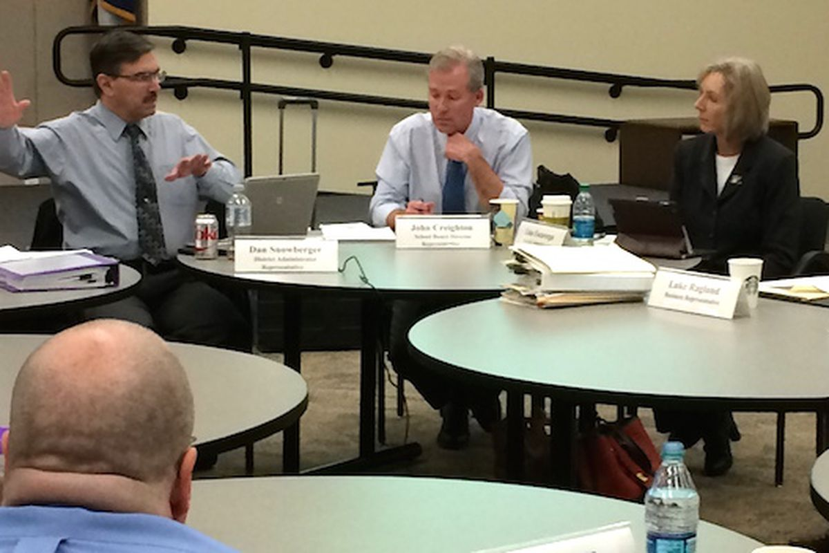 Testing task force chair Dan Snowberger (left) makes a point while John Creighton and Lisa Escarega listen.