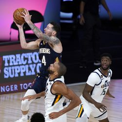 New Orleans Pelicans' JJ Redick (4) shoots over Utah Jazz's Rudy Gobert and Emmanuel Mudiay, right, during the second half of an NBA basketball game Thursday, July 30, 2020, in Lake Buena Vista, Fla. (AP Photo/Ashley Landis, Pool)
