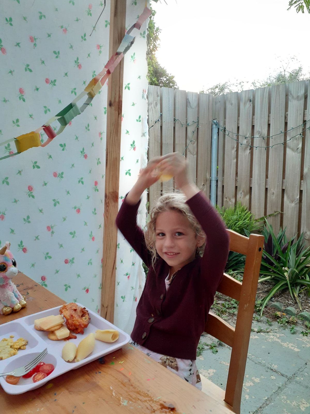 Mya Jardat's daughter sits in a sukkah, a temporary structure built by Jews to commemorate Shukkot, in anticipation of a guest joining the family for dinner at their home in Florida on Thursday, Sept. 30, 2021 .