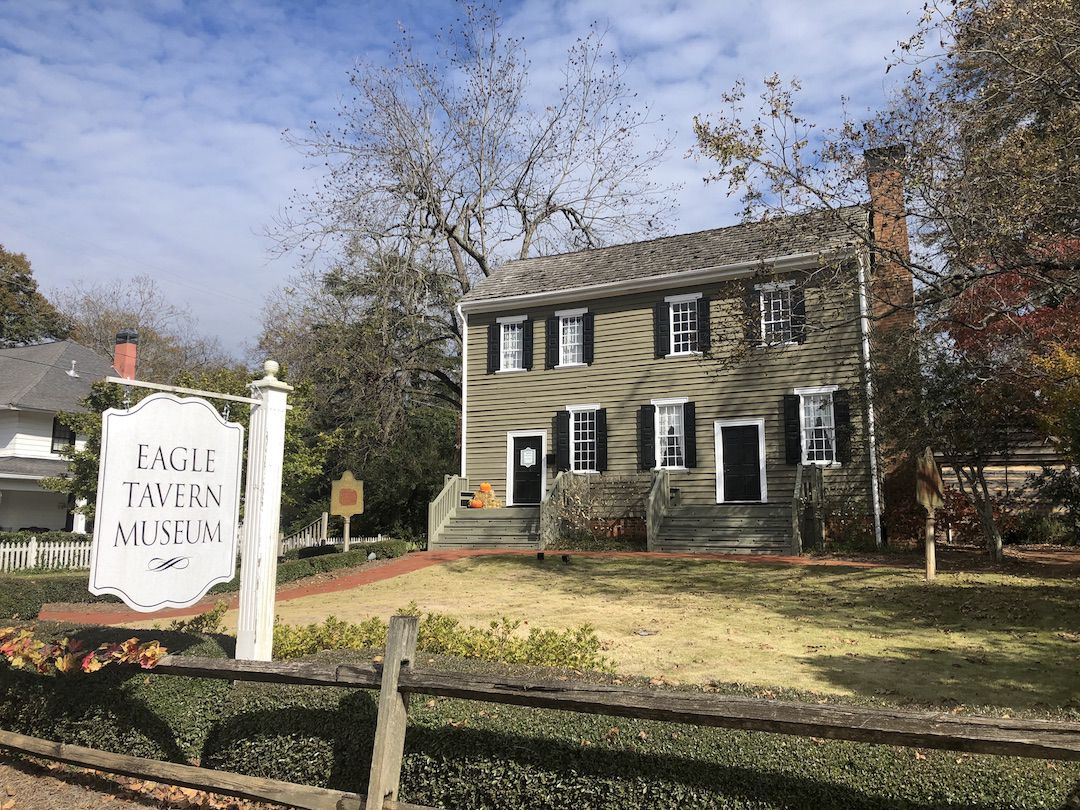 """Exterior view of two-story gray building with """"Eagle Tavern Museum"""" sign out front."""