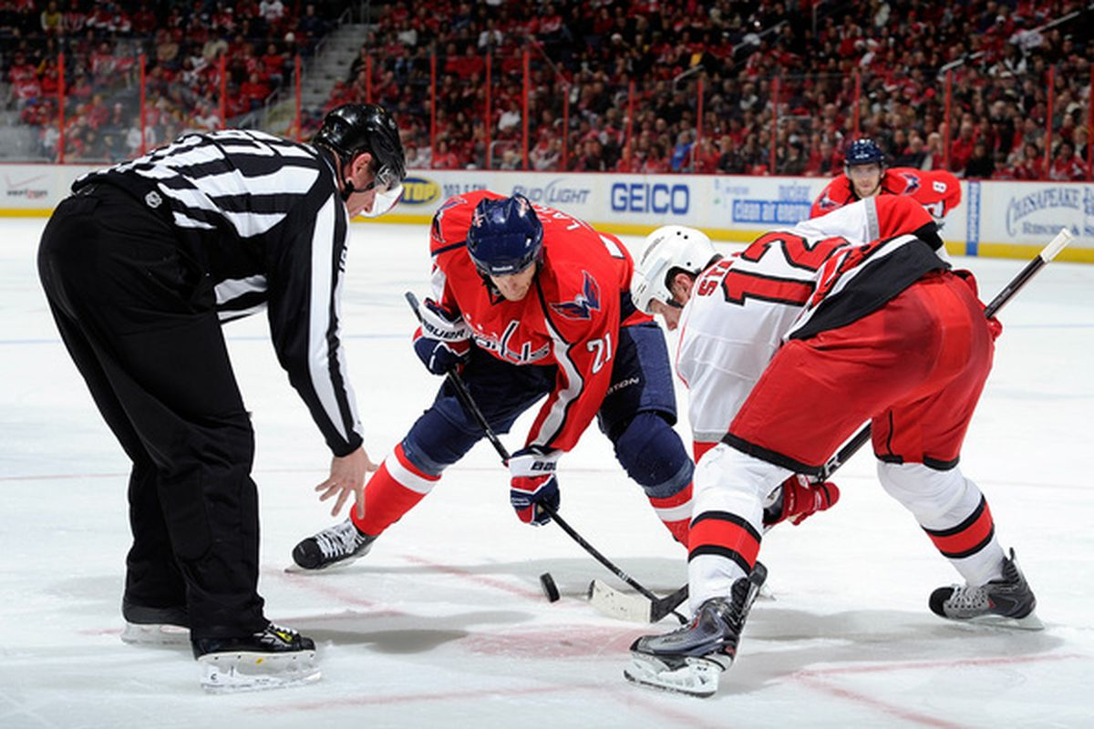 WASHINGTON - NOVEMBER 28:  Brooks Laich #21 of the Washington Capitals takes a face off against Eric Staal #12 of the Carolina Hurricanes at the Verizon Center on November 28 2010 in Washington DC.  (Photo by Greg Fiume/Getty Images)