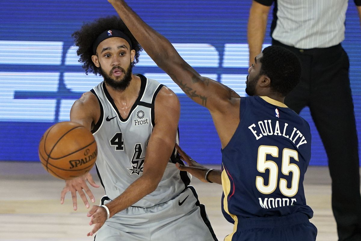 San Antonio Spurs' Derrick White passes the ball around New Orleans Pelicans' E'Twaun Moore during the first half of an NBA basketball game at The Field House.