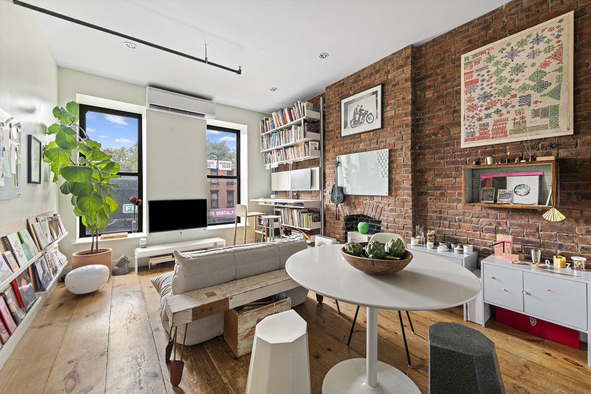 A living area with two large windows, a wall with exposed brick, pine floors, a planter, a round table, and a couch.