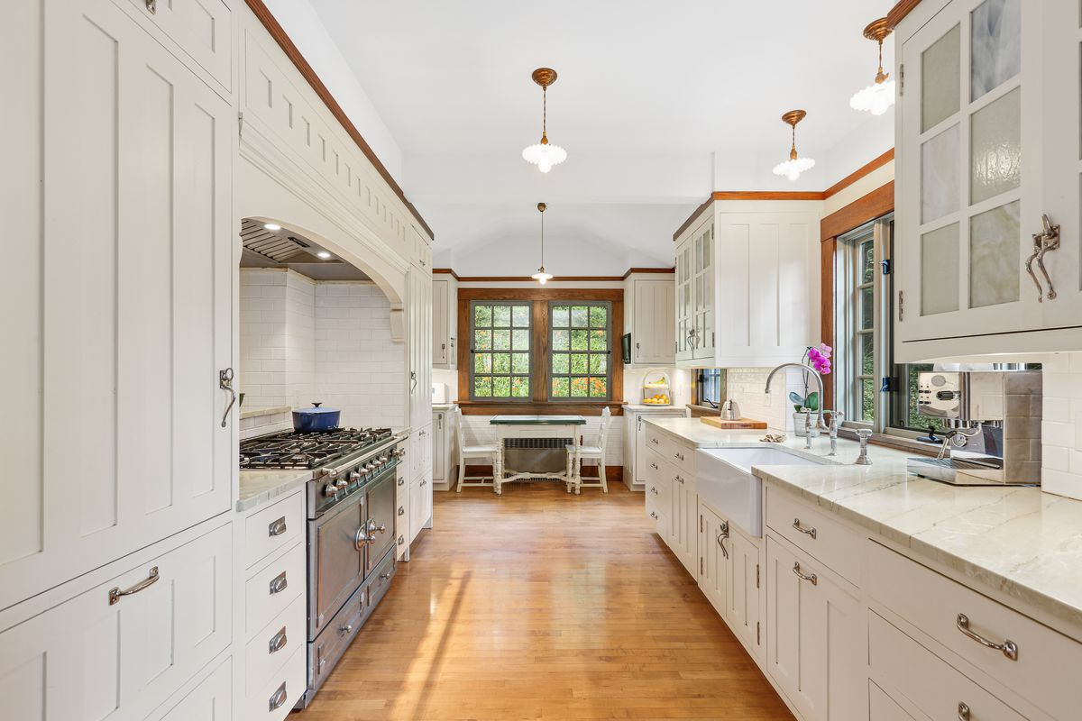 A long white kitchen with wooden cabinets and an eat-in on one side.