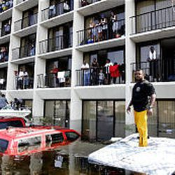 New Orleans police and volunteers use boats to rescue residents from a neighborhood on the east side of the flooded city.