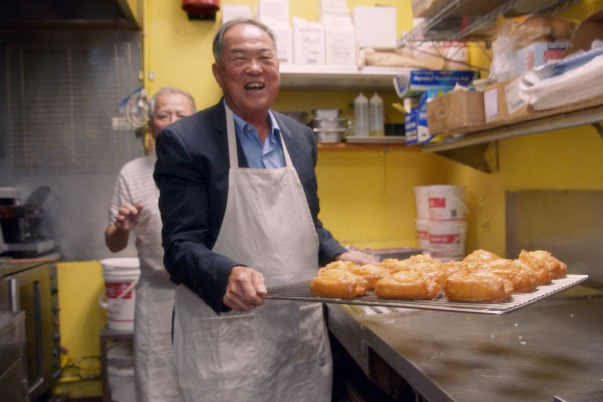 Ted Ngoy holds a rack of donuts in LA