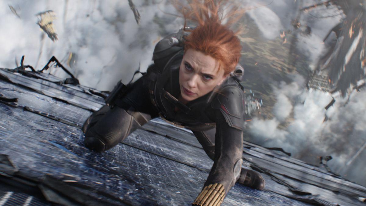 Black Widow slides her way down the side of a building amid falling debris in the Marvel Studios film Black Widow.