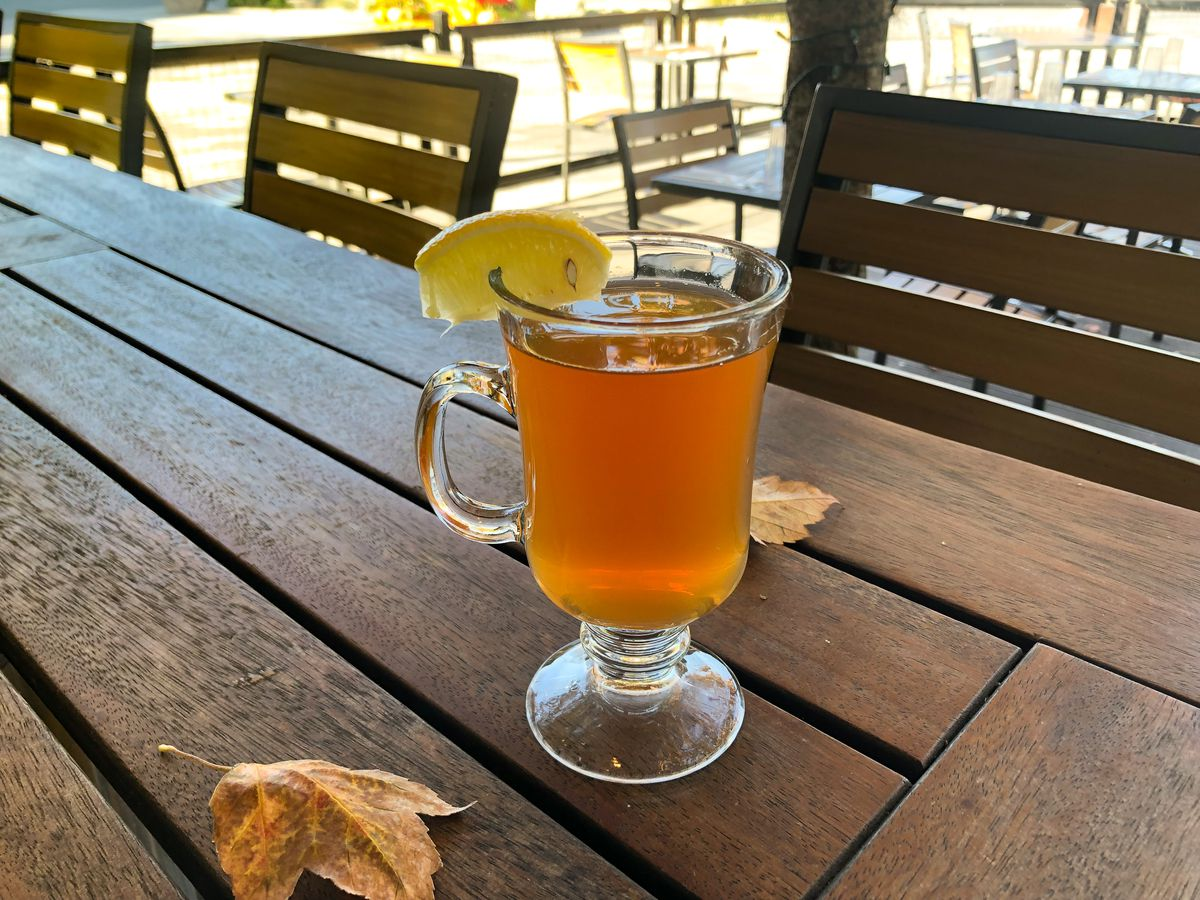 A hot toddy sits in a tall clear glass mug, embellished with a lemon wedge, on a wooden picnic table. A couple fall leaves are scattered on the table.