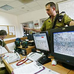 Israeli army Col. Tamir Hayman stands over surveillance computers in a command post in the Qalqiliya area.