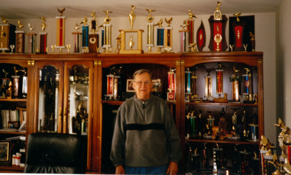 Tony Gacs in his office with many trophies won by his champion pigeons. | Family photo