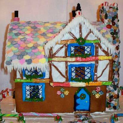A homemade gingerbread house in the style of a Tudor home.