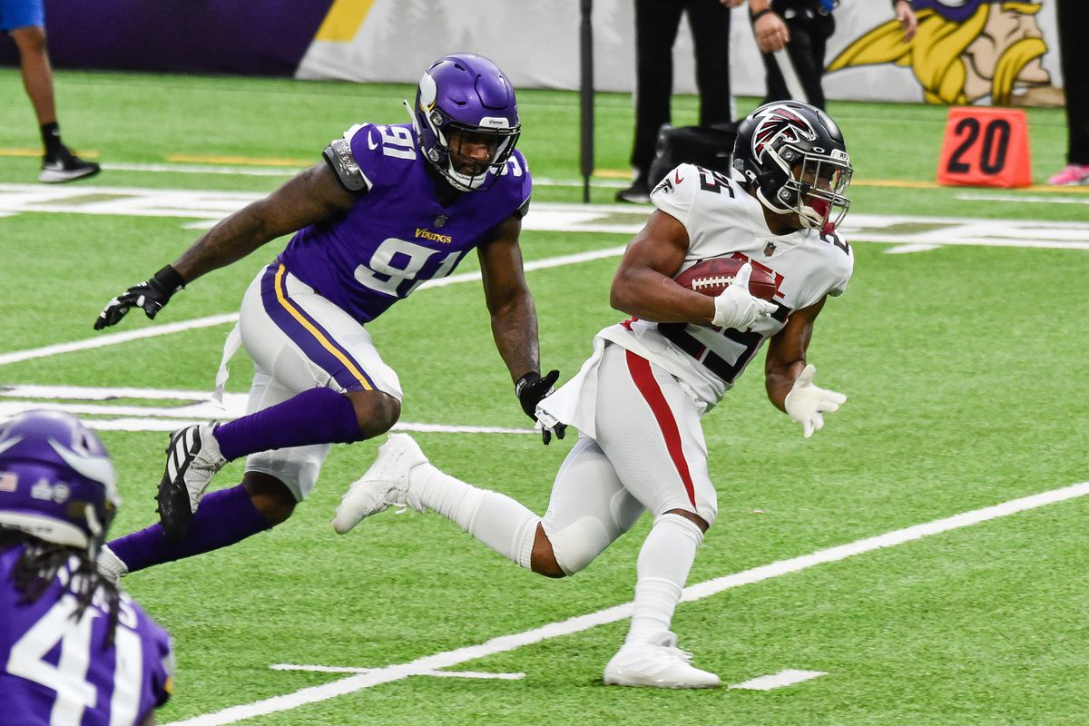 Atlanta Falcons running back Ito Smith (25) and Minnesota Vikings defensive end Yannick Ngakoue (91) in action during the game at U.S. Bank Stadium.