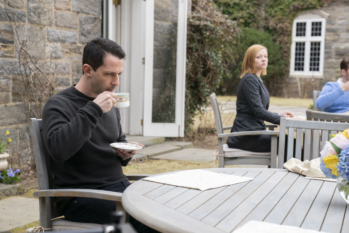 Kendall (Jeremy Strong) drinks as Shiv (Snook), a table over, keeps an eye on him.