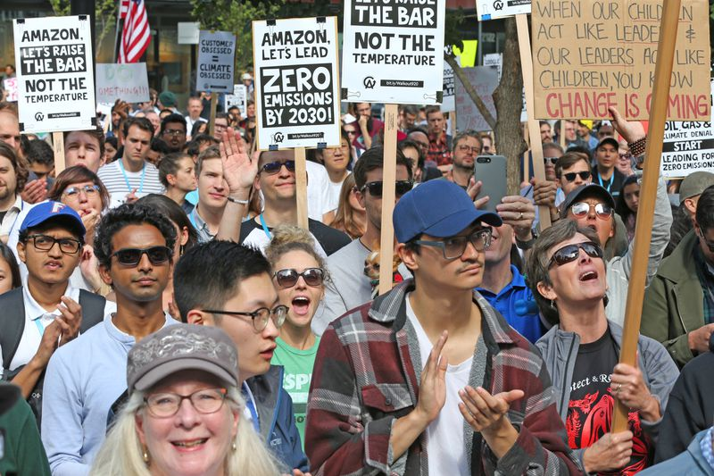 "A crowd of Amazon employees at a walkout carry signs that read, ""Amazon, let's lead: Zero emissions by 2030!"" and ""Amazon, let's raise the bar, not the temperature."""