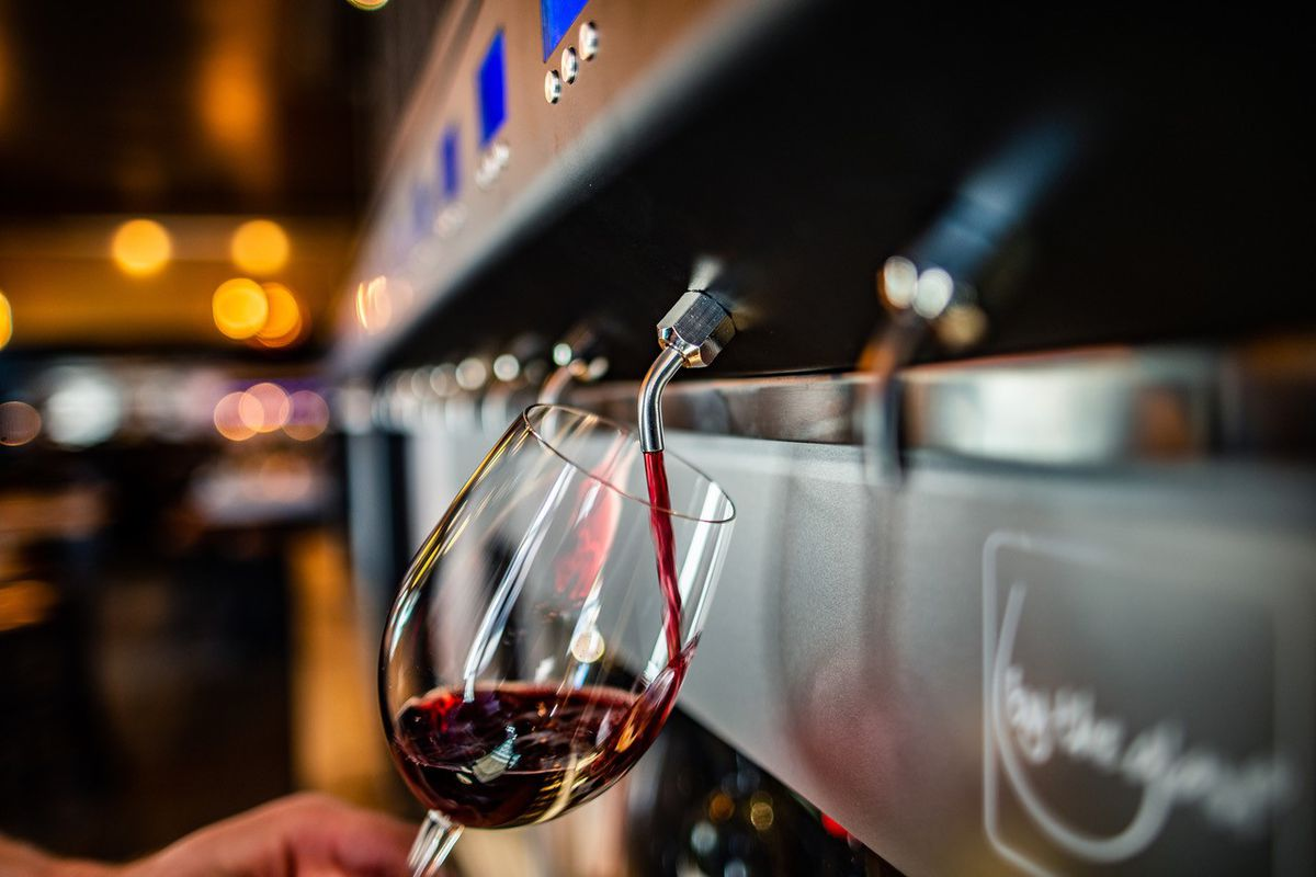 A tap pouring wine into a glass at self-pour bar Rapport