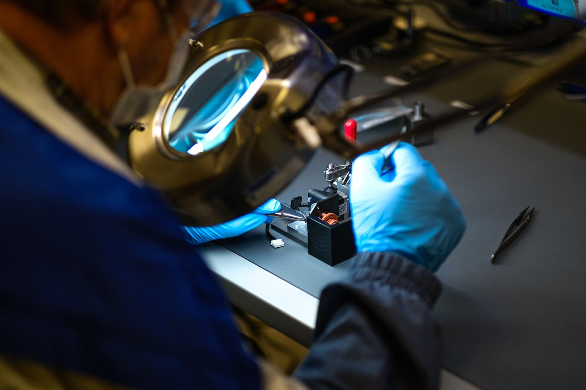 A worker wearing protective mask and gloves looks through a lit magnifying glass at a component on the table in front of them.