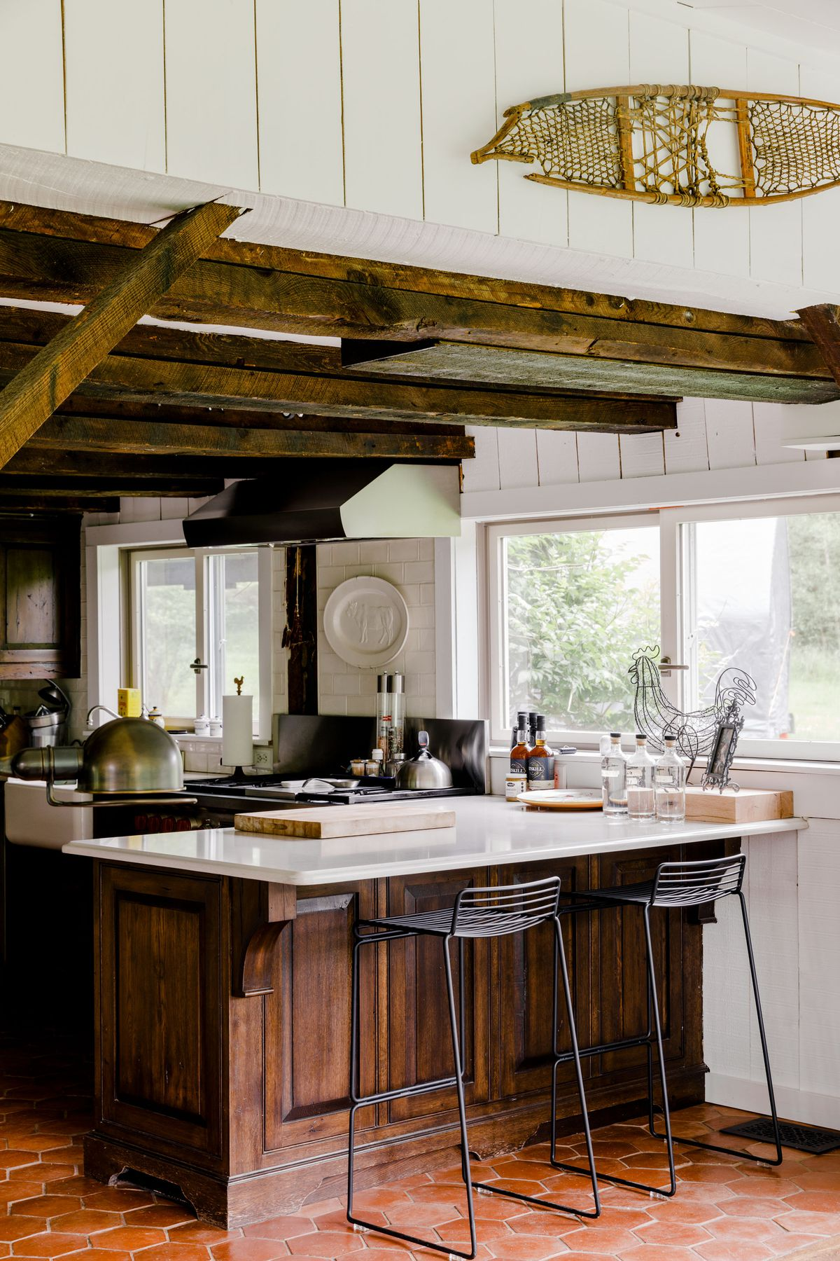 A kitchen with exposed wood beams on the ceiling, painted white walls, a counter, stools, and windows overlooking trees in a yard