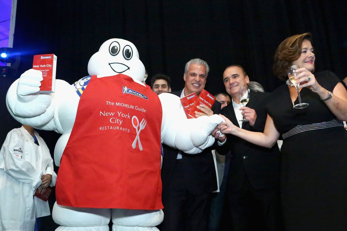 A person in a Michelin tire man costume stands with Eric Ripert, Jean-Georges Vongerichten and Claire Dorland-Clauzel