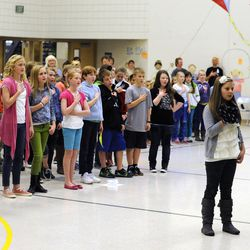 Addie Goettig leads the sixth grade class in saying the Pledge of Allegiance at Fox Hollow High School before being surprised by the early return of her father, Air Force Tech Sgt. Edward Goettig, on Thursday, March 6, 2014. Goettig had been deployed to Afghanistan since Aug. 27, 2013.