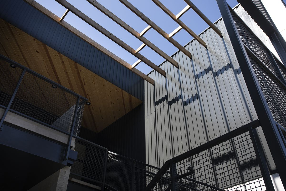 A black metal staircase brings workers to Purpose Built's new office in an open-air space.