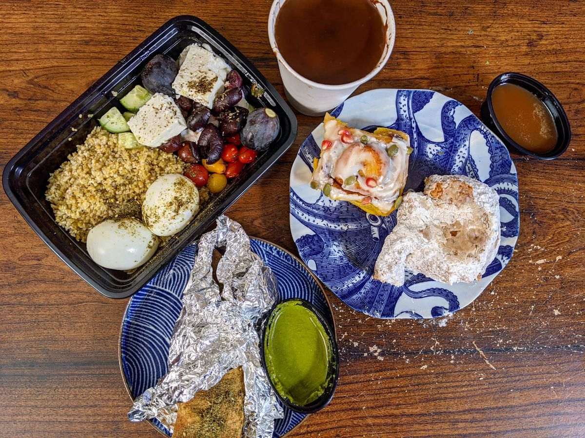 Overhead view of a wooden table full of breakfast takeout items: two pastries sit on a blue-and-white octopus plate, a paper cup holds a thick hot chocolate, and more
